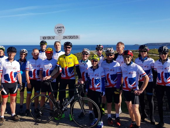 Pedal britain group of cyclists at land's end.