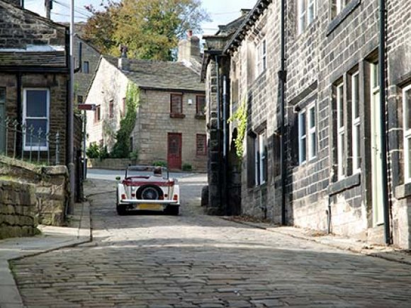Old classic car sriving up hill through cobbled streets.